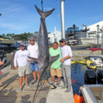 "2021 - 390 lb. Swordfish was caught in 1800 ft. deep of water on boat ""Beyond."" From left, Phil French, John Wolf, Jeff Bey and Harry Kennedy."
